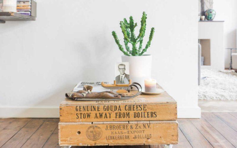 Voorbeeld van een uniek en persoonlijk interieurmeubelstuk. Deze bijzettafel is gemaakt van oude kaaskisten die een erfenis zijn. Daarop een mooie bos bloemen en persoonlijke herinneringen.