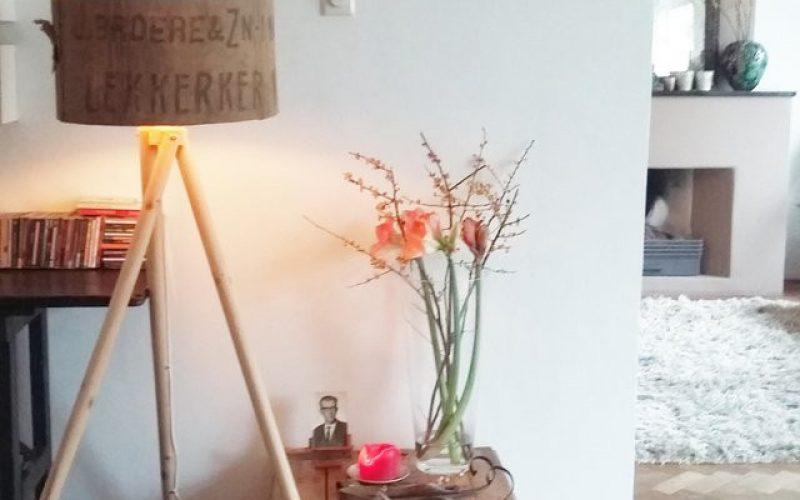 Voorbeeld van woonkamer in persoonlijke stijl met zelfgemaakte lampenkap door hergebruik van materiaal, oude planken vloer en een mix and match mt moderne meubels zoals een wollen vloerkleed en leren bankstel.