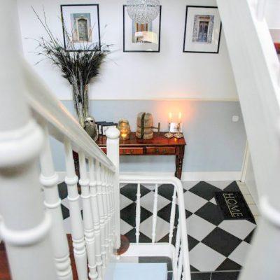 Gerenoveerd monumentaal trappenhuis met zwart witte tegels en sierlijke trapleuning