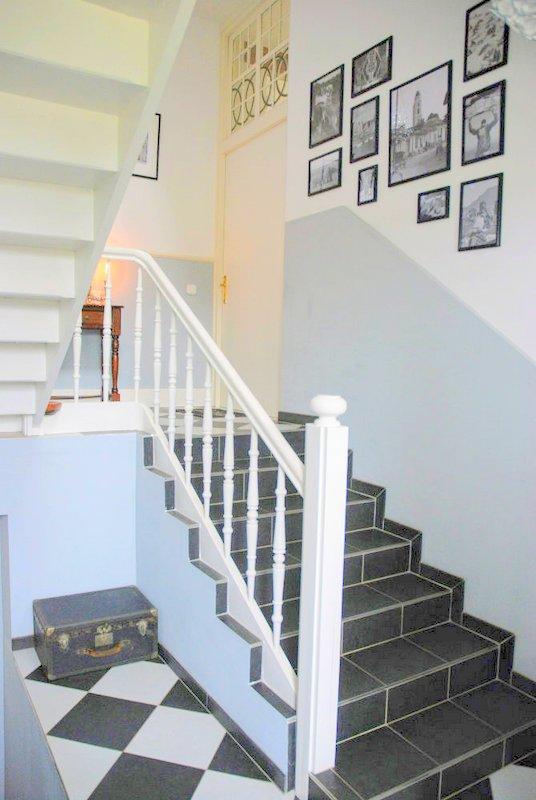 Binnenkijken na renovatie trappenhuis, metamorfose van de hal met zwart witte tegels en balustrades.