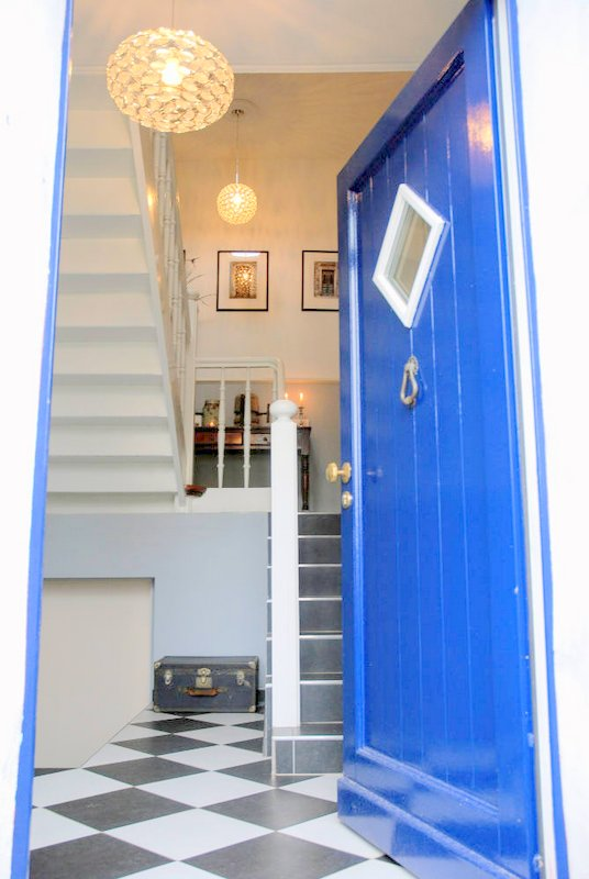 Entree van monumentaal trappenhuis, blauwe antiek vorodeur en zwart wit tegelvloer, trapopgang met sfeervolle verlichting.