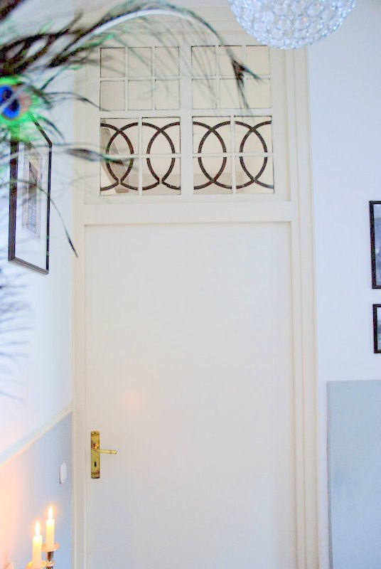 Interieurfoto van de verbouwde trapopgang hal van de oude directeurswoning, hier is ene prachtige oude deur te zien met glas in lood en ter decoratie pauwenveren op de sidetable.