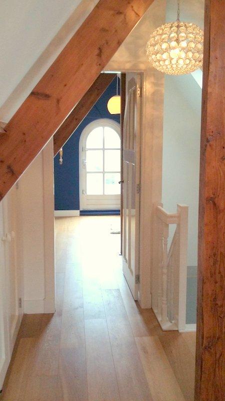 Doorkijk naar de slaapkamer op de zolder van het huis in Didam na de verbouwing, de oude balken en de op maat gemaakte deur en eikenhouten parketvloer.