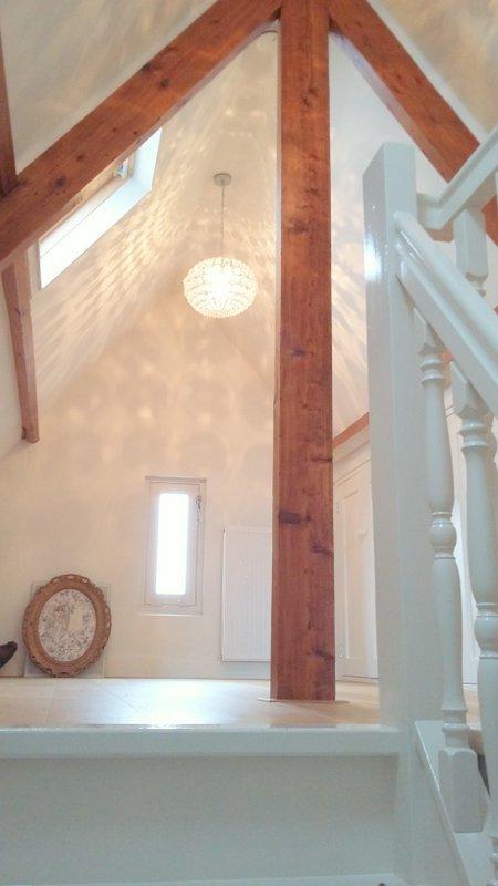 De verbouwde zolder in Didam gezien vanaf de op maat gemaakte trap, de oude houten balken zijn naturel kleurig gerestaureerd en de basis is wit met een eikenhouten vloer.
