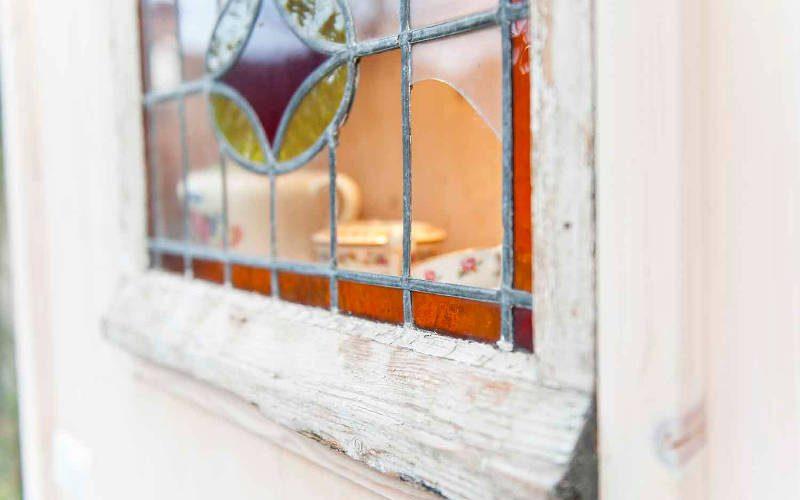 Oud glas-in-lood raam dat is hergebruikt in een duurzaam intreieuronwrp voor een duurzaam tinyhouse