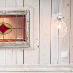 Duurzaam wonen met hergebruik van materialen zoals dit oude glas in lood raam dat is hregbruikt in een tuinhuis. Duurzaam interieurontwerp