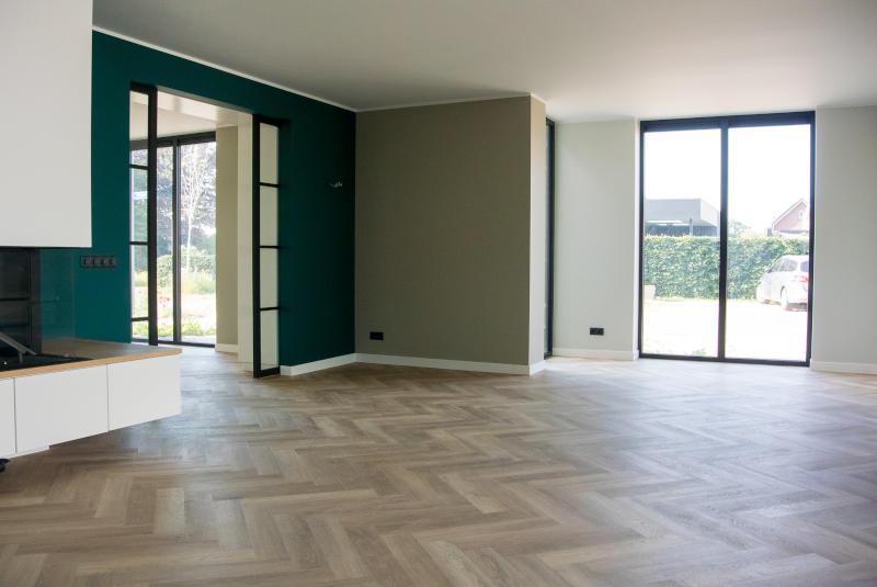 woonkamer van nieuwbouw woning in Wehl met groene muur en visgraatvloer en zwarte houten schuifdeuren en openhaard